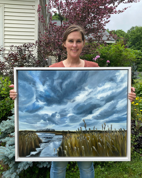 Brittany Soucy holding one of her paintings
